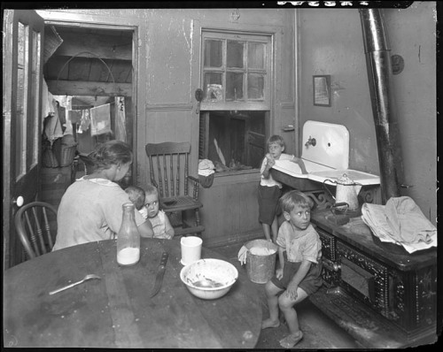 "Interior of tenement house [children and adult in kitchen]September 1925Hughes Company (for ""Community Fund"")8x10 inch acetate negativeBaltimore City Life Museum CollectionMaryland Historical SocietyMC6340 .2 A location for this photograph was not provided but considering that it was taken by  Baltimore-based Hughes Company, and the fact that it was collected by the Baltimore City Life Museum and not noted as non-Maryland, it is more than likely Baltimore."
