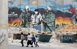 Children walk in front of a mural painted on part of Israel's controversial barrier at Aida refugee camp in the West Bank town of Bethlehem, ahead of Nakba May 14, 2012. On May 15 Palestinians will mark Nakba, or catastrophe, of Israel's founding in a 1948 war, when hundreds of thousands of their brethren fled or were forced to leave their homes. (REUTERS/Ammar Awad)