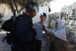 A Palestinian woman pleads to an Israeli riot policeman not to detain a boy who took part in protests in the east Jerusalem Arab neighborhood of Issawiya on May 15, 2012, marking Nakba day, which commemorates the exodus of hundreds of thousands of their kin after the establishment of Israel state in 1948. The Palestinian boy was later taken away by Israeli police. (AFP PHOTO/AHMAD GHARABLI)