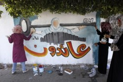 "Palestinian women paint a mural with the word in Arabic that reads, ""We will return"" in Gaza City on May 15, 2012, as Palestinians and Arab-Israelis marked Nakba day, which commemorates the exodus of hundreds of thousands of their kin after the establishment of Israel state in 1948. (AFP PHOTO/MOHAMMED ABED)"