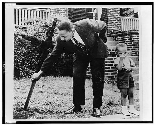"""Martin Luther King, Jr., pulling up a cross that was burned on the lawn of his home, as his son stands next to him."" Atlanta, Georgia - 1960. (Library of Congress)"