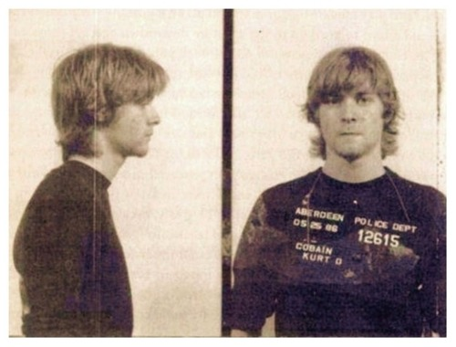 "Kurt Cobain's mugshot, from when he was arrested for spray painting ""God is Gay."""