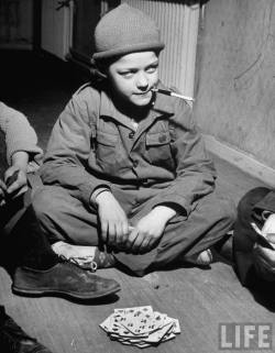 Young student smoking a cigarette while playing a card game Photographer: Mark Kauffman Children's Village For Troubled Children, Stockholm, Sweden, May 1949. © Time Inc.