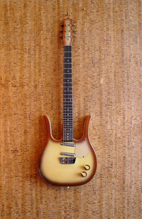 Danelectro model 4123 1963-1969Masonite, Poplar, Rosewood Also known as the Guitarlin, the Danelectro 4123 is remarkable not only by shape but by sound: Its extra long 31 frets neck adds a mandolin range.