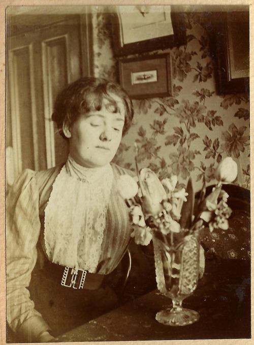 Edwardian woman contemplating a vase.