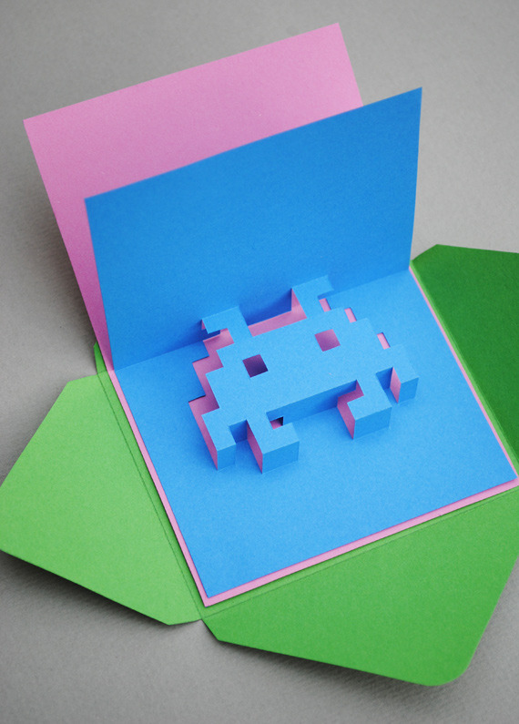 prostheticknowledge:  8-Bit Pop-Up Cards  Two ways to create your own: firstly, a tutorial from Mini Eco to create your own Space Invader and pixel skull:  Hello! Remember that pixel heart card I made a while back? Well it has been one of my most popular tutorials to date so I thought I would add another few designs to the collection. Meet 'space-invader popup' and 'skull popup' … You definitely need a craft knife (and a steady hand) to make these cards this project is only really suitable for adults or teenagers.  Full tutorial here If, on the other hand, you would like to design your own, there is a piece of software that has been around for years called Pop-Up Card Designer from Japan:   The latest version is Ver.2.1.1  Pop-up Card Designer is a Windows application, which generates unfolded patterns of Pop Up Cards. With simple interface, you can get unfolded pattern of your original Pop Up Cards. There is a limitation on the number of grids until you enter a password. Please purchase a password if you want to design more detailed work and to continue the use of this software.    This piece of software comes in both free and Pro versions, which you can check out here