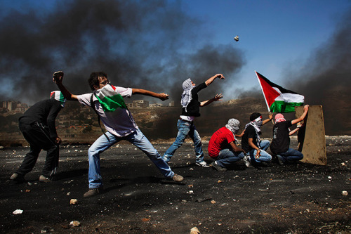 zerevolution:  Masked Palestinians throw stones at Israeli troops during clashes outside Ofer military prison. Photograph: Bernat Armangue