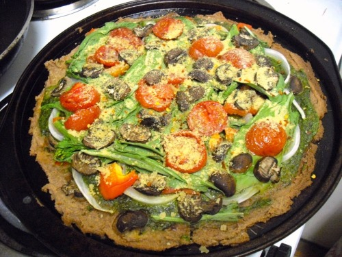 "reblogged from vegandurance:  Another Thrive-inspired pizza, with a chickpea/sunflower seed crust and pesto sauce! Ingredients: Crust2 cups ground sunflower seeds1 cup sprouted chickpeas (can use cooked chickpeas as well)1/4 cup coconut oil/hemp oil mix1/4 cup coconut oil1 tsp cumin1 tsp curry powder1/2 tsp turmericSea salt to taste Sauce (my homemade vegan pesto!)2 cups fresh basil leaves3 cloves garlic1/4 cup pine nuts4.5 Tbs extra virgin olive oil3 Tbs nutritional yeast2 Tbs Galaxy Vegan Grated Topping (optional, or use nutritional yeast) Sea salt to tastePepper to taste  Toppings (can use anything you want, really)Grape tomatoes, halvedBaby bella mushroomsYu choy Sweet onionRed pepper flakesNutritional yeast (as you can tell, I love this stuff)  Directions:For crust:  Put in food processor until desired consistency is reached.  Spread on a lightly-oiled or parchment paper-covered pizza pan . For sauce: Put basil and nuts in food processor until desired consistency is reached.  Slowly add in oil.  Add seasonings, salt, and pepper last to taste. Bake in over for about 45 min - 1 hour at 300 degrees. So nutritious, wholesome, and rich.  A heads up that the pizzas are not what you would expect from traditional ""pizza,"" and might not hold together as slices!  A fork (and big appetite) is recommended.  Thanks Brendan Brazier for the inspiration!"