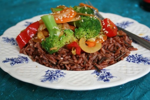 Ginger Vegetable Stir-fry with Camargue & Wild Rice Serves 2-3 Ingredients 10 small broccoli florets 2 small carrots thinly sliced 1/2 small tin bamboo shoots 1 cup shredded cabbage 1 small onion 1 large pointed red pepper 1.5 inch piece of fresh ginger, roughly chopped to retain as much gingeriness as possible :) 1 large garlic clove 1 tsp of powdered ginger 4 Tbs Tamari soya sauce 2 Tbs olive/ sesame oil 1 cup mixed red Camargue & wild rice (uncooked) 1 Tbs sesame seeds If you can't find the wild & Camargue rices combined, Camargue on its own is fine. Method 1. Cook the rice according to pack instructions. Begin by frying the onion with the oil and half of the garlic and fresh ginger. Boil the broccoli for 2-3 minutes, then drain and allow to dry. 2. Add the carrot and pepper and stir-fry for another 3 minutes. Meanwhile in a small bowl combine the Tamari, powdered ginger and remaining garlic and ginger.  3. Add the broccoli, cabbage and bamboo shoots and pour over the tamari mixture, stir through for a further minute, then place on top of the Camargue & wild rice. Finally, sprinkle the sesame seeds over the top. - You can cook the vegetables for longer if you prefer, the stated times are for quite crunchy, just cooked veg.