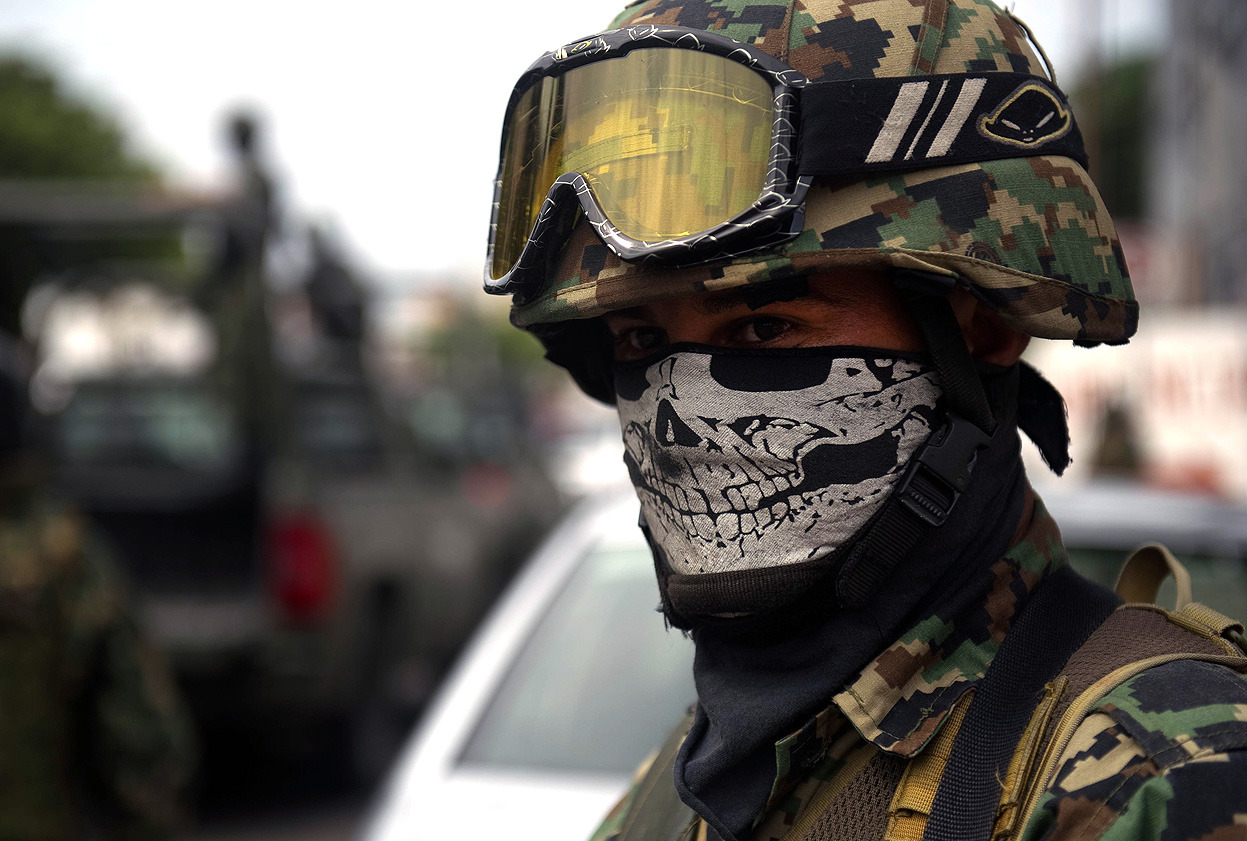 "From Mexico's Drug War: 50,000 Dead in 6 Years, one of 44 photos. Here, a masked Mexican soldier patrols the streets of Veracruz, on October 10, 2011. Soldiers of the Army, Navy and members of Federal Police patrol the streets of the city as part of ""Veracruz Safe Operation"" after a rising tide of violence plaguing this tourist city. (Yuri Cortez/AFP/Getty Images)"
