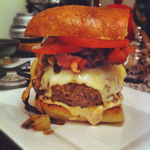 HomeCookin': Lean Mean Burger Machine Homemade burger, Munster cheese, caramelized onion, bacon, tomato & chipotle crema  Sometimes you just gotta have a little  big burger for dinner.  On a night that followed hours laying in the sun on our roof, we decided to really *summer* it up and make burgers…  1lb lean ground beef  salt & fresh cracked pepper Sriracha or good hot sauce 1 glove finely grated Garlic  1 Ciabatta loaf - cut in half to serve two burgers 1 tomato - sliced  6 slices of bacon 1/2 large onion sliced into rings 4 slices of Munster cheese  1/4 cup Sour cream 1 chipotle in adobo  ** In a bowl gently mix the ground beef with grated garlic, salt & pepper and about a teaspoon of hot sauce. Mold into burger mounds, and round & tighten. In a large fry pan, cook the bacon until crispy. Rest on paper towels. Reserving some of the bacon fat, cook the onions until caramelized. Hey, I won't tell anyone if you splash a little beer in there. Hell, it's only gonna make them taste AMAZING.  Push onions to the side of the pan.  Drizzle a little olive oil in the pan and then place the burger down to cook on a med to high heat.  I cooked my burgers about 6 mins on either side.  Once you flip the burger (after the first 6 mins) add the sliced cheese on top of each. The last 3 mins, I put a lid on the pan so the cheese really melted.   Take out the meat to rest.   Drizzle your Ciabatta with a little oil and put face down in the pan to warm.  I added the bacon back on top of the onions to warm up.  In a small bowl, mix sour cream, chipotle and a squeeze of lime juice.   Assemble burgers. Bun, sour cream, burger w cheese, onions, bacon, tomato, sour cream, bun.  DONE.  Deeeeeelicious.