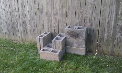 Here's my tentative design for the cinder block planter. One thing you will notice is how worn and grimy the blocks look compared to the photos of cinder block planters you see on pinterest—those people must be using brand new blocks. But I actually don't mind the more rugged look. I'm going to try to plant herbs in here this weekend. One challenge in laying this out was that it turns out we have six blocks of one size and three blocks of a smaller size, so the smaller size didn't stack up attractively on top of the larger. I think I worked it out and maintained a good amount of planting area for only having nine blocks!