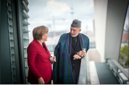 "Bag's Take-Away: Remember that Karzai was chosen for his job because of his Western sympathies and commercial ties? This image harkens back to that and reminds us no matter how the West thinks of him, he still has to govern a ""third world"" country. Not saying he's a good or bad guy in either role, just noting that he's much closer to who the West thought he was when away from home.  via The New York Times Lens (credit: Guido Bergmann/ Pool photo caption:  chancellor Angela Merkel of Germany with President Hamid Karzai of Afghanistan on the roof of the Chancellery in Berlin. They met to discuss the NATO summit in Chicago this weekend and the signing of a bilateral co-operation agreement between the two nations.) Visit BagNewsNotes: Today's Media Images Analyzed ————— Topping LIFE.com's 2011 Best Photo Blogs — also follow us on Twitter and Facebook."