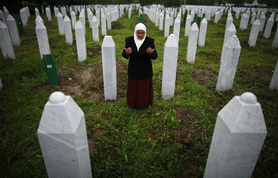 Mejra Dzogaz prays near the graves of her two sons before the television broadcast of the court proceedings of former Bosnian Serb general Ratko Mladic's in Potocari, near Srebrenica, Bosnia and Herzegovina May 17, 2012. Mejra's husband, three sons and a grandson were killed during the Srebrenica massacre in 1995 by a Serbian army unit commanded by Mladic. The Bosnian Serb general made a throat-slitting gesture to a woman who lost her son, husband and brothers in the Srebenica massacre at the start of his trial on Wednesday for some of the worst atrocities in Europe since World War Two. [Credit : Dado Ruvic/Reuters]
