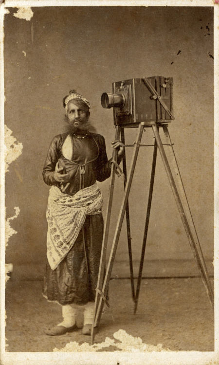 ca. 1875, [albumen portrait of Mohan Lal with His Camera]  The subject here is likely the painter-photographer Mohan Lal, posing with his camera and holding the lens cover in his hand. A number of Mohan Lal's pictures are documented in the Udaipur City Palace photographic archives. Most courts either maintained a photographer in the same manner that court painters were employed in the household, or else, they increasingly turned to the services of commercial photographic studios, which arose rapidly in India.  via the Metropolitan Museum of Art, Photographs Collection