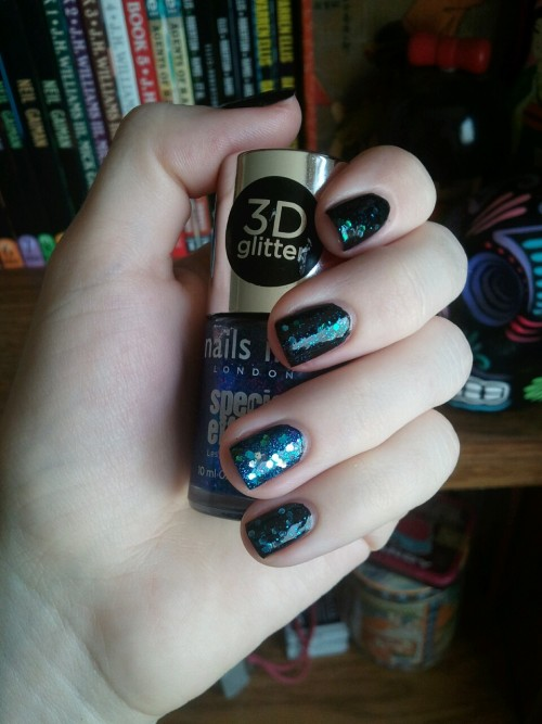 toxicnotebook:  Today I glitterbombed my nails. Ring: Milani Teal Jewel FX over Nails INC Connaught Square over CG Smoke and Ashes Rest: Deborah Lippman Across the Universe over CG Smoke and Ashes Originally, I was going to only have Smoke and Ashes on my non-ring fingers, but apparently I have to layer everything now! And here's a close-up of the ring so you can see the purple glitter:  I do love the Nail INC 3D glitters, even though they eat up top coat. I have a few things to announce today, so stay tuned!