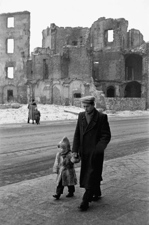 A father and son walking past houses in Warsaw, still in ruins, 12 years after the end of WWII. Warsaw, Poland - 1957