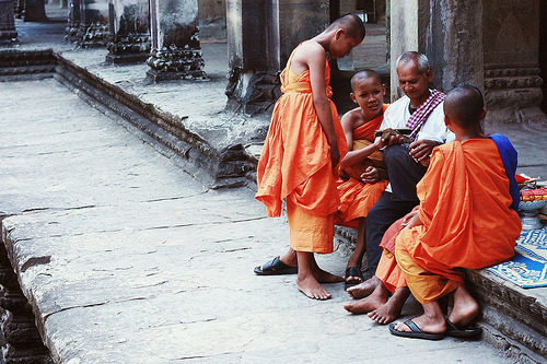 Learning —-  A group of young monks get tips from an elder in the temple.