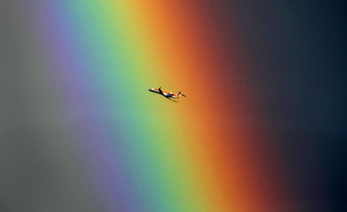 An airplane passes in front of a rainbow above the Mediterranean sea in Nice, southeastern France on Aug. 5, 2010. (AP Photo/Lionel Cironneau)