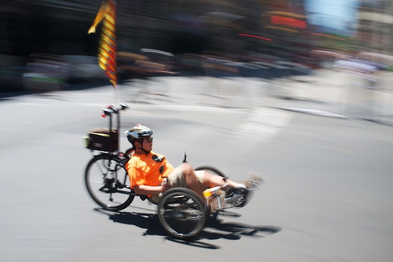 Recumbent Racer Yes, the obsession with panning shots of people in bikes and cars and all kinds of vehicles continues — this time with a guy shredding through Fifth Avenue on a recumbent bike.  He better be careful though. Being so low to the ground means vehicles with low visibility (SUVs and trucks) might not see him. And that's all I have to say about that.