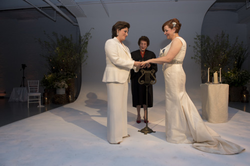 Christine Quinn and Kim Catullo exchanging rings before Judge Judith Kaye. Photo credit to William Alatriste.