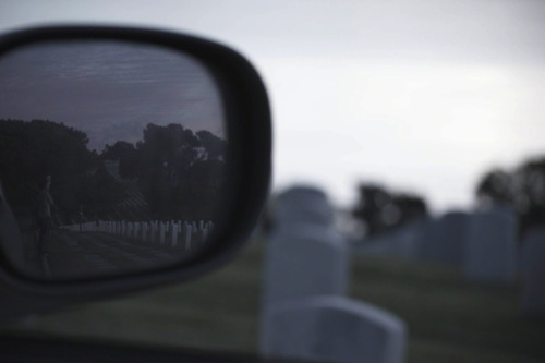 This was taken at the Rosecrans National Cemetery located in Point Loma which is a Peninsula that stretches out from San Diego into the Pacific.  I was wondering around near the lighthouse and tide pools located at the end of the point and stopped by the cemetery before going home.  I was just about to leave when I saw this couple framed in my passenger side mirror.  I thought the composition was really cool and somewhat erie at the same time so I pulled out my camera and snapped a few shots. Photographer: Steven WilliamsLocation: San Diego, CAsteveslefteye.comfacebook.com/steveslefteyefacebook.com/isstevestillalive@stevestillalive (via Uncategorized)