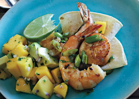 Mexican Seafood Sauté with Avocado-Mango Salsa 6 Servings  Ingredients  salsa 1 mango, peeled, pitted, diced (about 1 1/2 cups) 1 large avocado, peeled, pitted, diced 1 large shallot, chopped (about 1/4 cup) 1 jalapeño chile, seeded, finely chopped (about 1 1/2 tablespoons) 2 tablespoons finely chopped fresh mint 2 tablespoons fresh lime juice   seafood 1/3 cup chopped shallots (about 2 medium) 1/4 cup fresh lime juice 1/4 cup tequila 2 garlic cloves, pressed 2 teaspoons ground cumin 1/3 cup plus 4 tablespoons olive oil, divided 1 1/2 pounds uncooked jumbo shrimp, peeled, deveined 1 pound sea scallops, side muscles removed 12 green onions, thinly sliced (white and pale green parts only; about 1 1/2 cups) Lime slices    Preparation  salsa  Mix all ingredients in medium bowl. Season to taste with salt. Cover and chill. DO AHEAD Can be made 2 hours ahead. Keep chilled.    seafood  Whisk first 5 ingredients in small bowl to blend. Gradually whisk in 1/3 cup olive oil. Season marinade to taste with salt and pepper.   Place shrimp in large resealable plastic bag. Place scallops in another large resealable plastic bag. Pour marinade into bags, dividing equally (about 1/2 cup each). Seal bags; turn to coat. Chill at least 30 minutes and up to 1 hour.   Drain shrimp and scallops; pour marinade into small saucepan. Bring marinade to boil; set aside.   Pat scallops dry. Heat 2 tablespoons oil in heavy large skillet over medium-high heat. Add scallops to skillet and sauté until beginning to brown, about 1 1/2 minutes per side. Transfer to large bowl. Add remaining 2 tablespoons oil to skillet. Add shrimp and green onions; sauté until shrimp are almost opaque in center, stirring often, about 3 minutes. Return scallops with any accumulated juices to skillet. Add boiled marinade. Simmer until seafood is just opaque in center and mixture is heated through, 1 to 2 minutes. Transfer to large shallow bowl. Garnish with lime slices. Serve with salsa