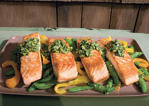 Salmon with Snap Peas, Yellow Peppers, and Dill-Pistachio Pistou4 Servings  Ingredients  1/3 cup chopped fresh dill 1/3 cup finely chopped green onions (about 2) 1/2 cup shelled natural pistachios or almonds, toasted, finely chopped 1/4 cup plus 1 1/2 tablespoons pistachio oil or extra-virgin olive oil 2 yellow bell peppers or orange bell peppers, cut into 1/2-inch strips 1 pound sugar snap peas, trimmed, strings removed 1 garlic clove, minced 1/4 cup water 4 6-ounce salmon fillets    Preparation   Mix dill, green onions, pistachios, and 1/4 cup oil in medium bowl. Season to taste with salt and pepper. DO AHEAD Pistou can be made 2 hours ahead. Let stand at room temperature.   Heat 1/2 tablespoon oil in heavy large skillet over medium-high heat. Add peppers and sauté until beginning to soften, about 2 minutes. Add snap peas, garlic, and 1/4 cup water; sprinkle with salt. Sauté until vegetables are just tender and water evaporates, 2 to 3 minutes. Stir in 1 rounded tablespoon pistou. Transfer vegetables to platter; tent with foil to keep warm. Reserve skillet (do not clean).   Heat remaining 1 tablespoon oil in reserved skillet over medium-high heat. Sprinkle salmon with salt and pepper. Place salmon, skin side down, in skillet; cook until skin is crisp, about 3 minutes. Turn salmon and cook until almost opaque in center, about 3 minutes longer. Arrange salmon fillets over vegetables on platter. Spoon some pistou down center of each fillet and serve, passing remaining pistou alongside.