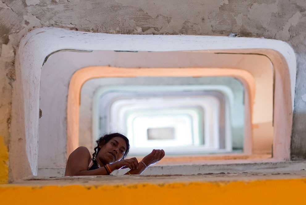 "© Andre Penner, Feb. 23, 2012, Sao Paulo / Brazil A woman looks down from the staircase in the occupied Prestes Maia building in downtown Sao Paulo. Occupied in 2002 by about 350 homeless families, the building lacks electricity, elevators and running water. The families are part of Brazil's ""roofless"" squatter movement which has been around for years and hasn't abated despite the nation's economic boom. Squatters say their meager incomes, often earned in Brazil's informal economy, would never allow them to afford rent, even in slums."