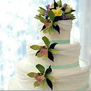 (via A four-layer cake is draped with white fondant and topped with hand-made sugar orchids and roses. || Colin Cowie Weddings)