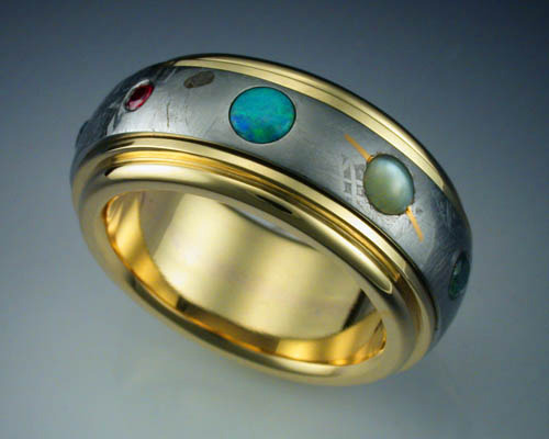nice-bed-can-i-slytherin:   This ring features a complete band of Gibeon Meteorite framed and mounted in an 18k gold band. The meteorite has been etched with nitric acid to reveal the characteristic patterns, or Widmanstatten figures, of iron meteorites, and set with 9 gemstones representing the planets of our Solar System. Mercury is represented by a rust colored Sapphire, Venus a golden Sapphire, Earth an irradiated blue Diamond, Mars a Ruby, Jupiter an Opal, Saturn a Cats Eye Chrysoberyl with an inlaid 24k gold ring, Uranus a green Sapphire, Neptune a blue Sapphire and Pluto a black Diamond. What really makes this ring special is that the band of meteorite spins independent of the gold ring, so when it is on, the planets rotate around the wearer's finger.