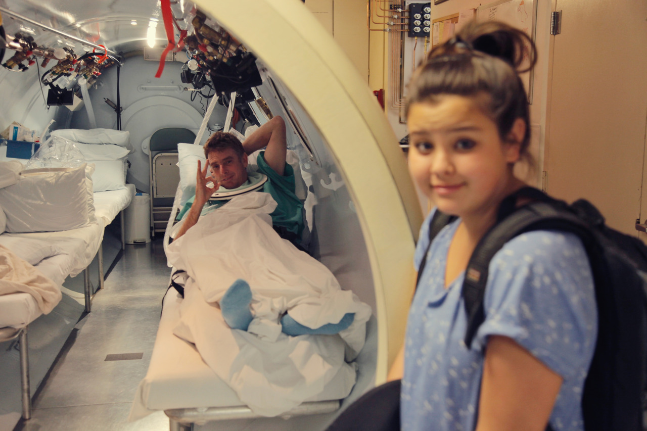 Mike's daughter Mira, waits for her father to get out of the hyperbaric chamber. - San Diego, California.