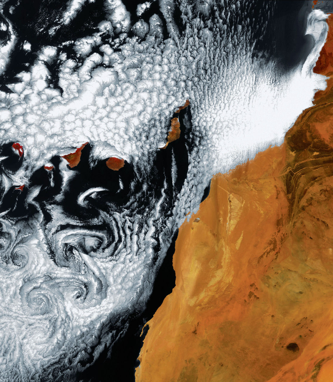 A satellite image of the Canary Islands with unique cloud formations, created by 'Von Karman vortices', off the coast of Africa (right) in the Atlantic Ocean. These vortices, named after aeronautical engineer Theodore von Karman, form as air flows around an object in its path, causing it to separate and create eddies in its wake. The clockwise and counter-clockwise spirals in this image were created as wind blowing from the north over the Atlantic was disturbed by the archipelago. The islands are (left to right): El Hierro, La Palma, La Gomera, Tenerife, Gran Canaria, Fuerteventura and Lanzarote. © ESA