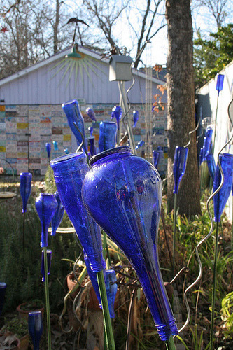 "unconsumption:  More yard art in Austin: Robert Mace's ""bottle prairie."" Old license plates cover the side of the building in the background. (photo by bubbaofthebubbles on Flickr)"