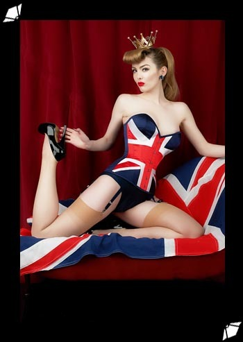 "I first thought about doing a Union Flag corset last Spring, to celebrate Prince William's and Kate Middleton's wedding. I thought it would be great as part of a window display, combined with lots of Union Flag bunting, but really didn't think people would be interested in buying it. I sketched a basic design and asked our factory to throw something together, explaining that it was only for a window display and that it didn't have ot be perfect. Well, they disagreed and were really excited a the challenge which resulted in the most fabulous (and it turns out, horribly expensive!) corset. We had it in our London boutique window for a couple of weeks and did take a few orders and that, I thought, was that.  When I was in our factory in January I started working on a range of Jubilee lingerie in red, white and blue, and started thinking about the corset again. I thought if we were going to do it, we'd really go for it! This time around we made it in the Extreme Laurie shape which takes 2"" more from the waistline than last year's Sophia shape. We also made it in two cup sizes for a perfect fit. Finally, we made a slight change to the flag design, changing the waist panels from blue to red which helps enhance the female form. The resulting corset really has had a great response, surprisingly those outside the UK are most enthusastic! The picture below, featuring Miss Miranda, was shot by Steve Hart in his Slough (UK) studio at the end of a very long day - not that you'd be able to tell!"