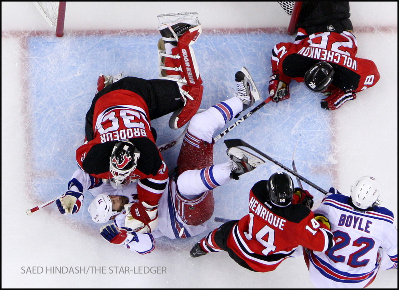 New Jersey Devils goalie Martin Brodeur (30) pounces onto New York Rangers left wing Mike Rupp (71) after Rupp crashed to the ice after he was tripped by New Jersey Devils defenseman Anton Volchenkov (28) in the 1st period during Game 4 of the Stanley Cup Eastern Conference Finals at the Prudential Center May 21, 2012.