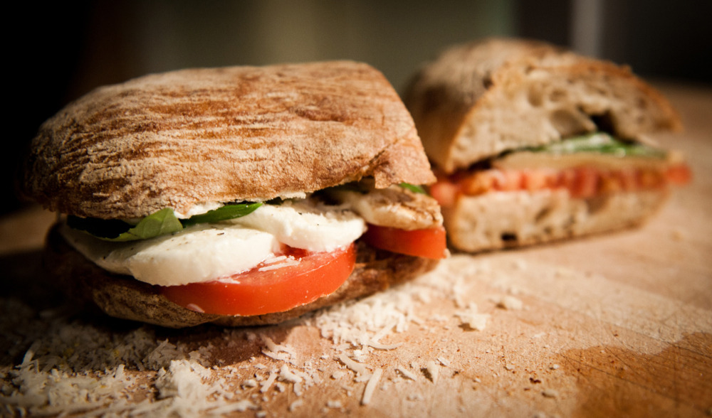 Mozzarella, tomato & basil If you know me, you'll know a man who thinks that there's little better than a slab or two of recently slaughtered animal to go between the two slices of bread in my lunchbox. That said, I'm happy to admit that after several years in the 'I'm-only-eating-nuggets' wilderness as a child, I'm now a firm fan of a less meaty filling, should the occasion call for it. Today's sandwich came from a casual chat with a friend at The Butty's favourite pub – The Euston Tap. His better half had requested a creation with a more Italian theme, and well, who are we to say no to a lady? This is a simple sandwich with fairly subtle flavours – no sticky sauces, and no big salads. First things first, the bread's a fresh ciabatta – baked, cut in half, then grilled to crisp the inside (important, as the ingredients here are very moist). Inside, there's thick sliced organic vine tomatoes, ripe and tasty. Crap tomatoes will ruin this sandwich, as they're providing so much of the flavour – if you skimp here, there'll be no taste at all come lunchtime. On top of the toms, sliced mozzarella – tearing is an option, but cutting it thick means you get a bit more bite in the butty. Finally, the garnish is simple a few fresh basil leaves, a few glugs of balsamic across the top of everything, and a grind of black pepper. As an extra, there's a dusting of grated parmigiano reggiano that I had left over from my dinner (Jamie Oliver's Proper Bloke's Sausage Fusilli – well worth a go, by the by) – should keep things nice and tart.  Of course, if you're making this the night before, then you might find yourself with a little to spare… so grab a slice of wholemeal, toast it, put on a scraping of butter (or, even better, a splash of extra virgin olive oil). Then just dice up whatever tomato you've got left, rip up the leftover mozzarella, and finish with some balsamic – that way, you'll know what you've got to look forward to in the morning.