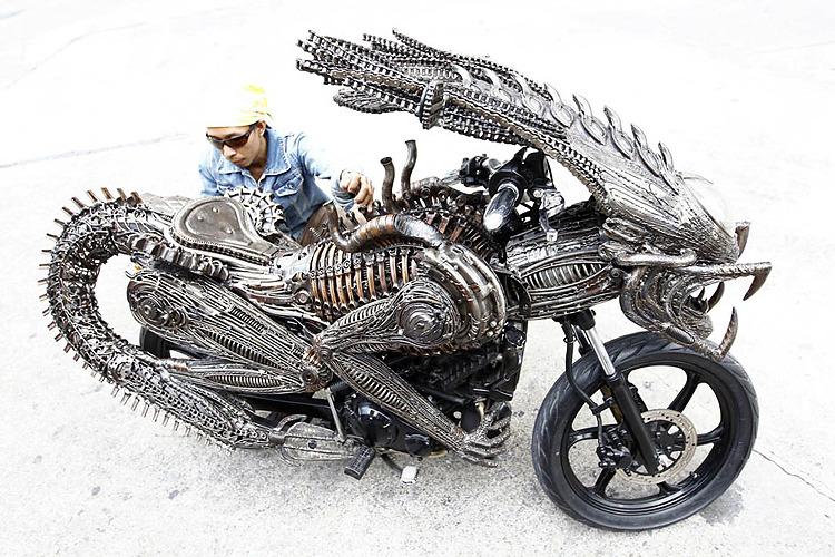 Alien Motorcycle  Alien prequel Prometheus doesn't hit theaters until June 1, 2012. So in the interim, let's take a trip down memory lane to the series' Alien vs. Predator installment. Are you there? OK, now throw in a motorcycle, a grip of recycled metal, and a superbly talented Thai sci-fi nut. Metalworker and all-around artistic genius Roongrojna Sangwongprisarn has not only brought to life his wicked vision of an Alien-Predator amalgamation, he's done it 1) using old car and bicycle parts, and 2) on top of and integrated into a motorcycle still capable of roaring (or possibly creeping—it's unclear what the bike was in its former life) down the streets of Bangkok.