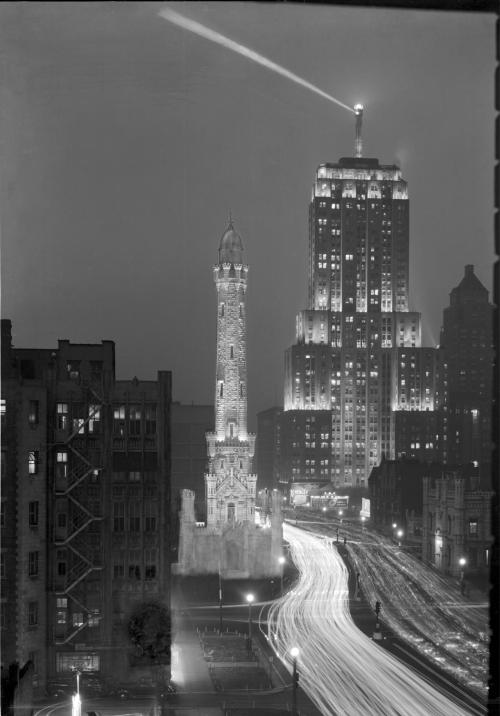 Night view of the Palmolive Building with the Water Tower in the foreground. The lights are from automobiles creating movement streaks on Michigan Ave., c. 1931. Photograph by Ken Hedrich. Want a copy of this photo? > Visit our Rights and Reproductions Department and give them this number: HB-00939-C. Connect with the Museum