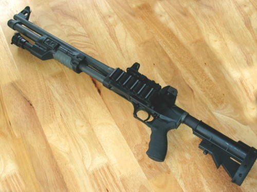 gunrunnerhell:  FN TPS (The TPS stands for Tactical Police Shotgun. This one has quite a bit of aftermarket parts added on. What's interesting about the TPS is that it comes from the factory with AR-15 style front and rear sights, as well as an AR-15 stock and pistol grip. It handles much like the rifle so officers and military personnel can get accustom to it much faster.)