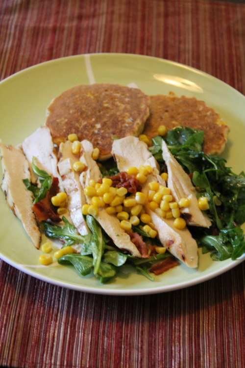 Grilled Chicken with Fresh Corn Cakes Inspired by: Southern Living Makes 4 servings  Preheat your grill to 350-400* In a small bowl grate zest from 3 lemons (1 tablespoon total). Squeeze juice from lemons until you have 1/4 cup. Whisk together lemon zest, 2 garlic cloves, 1/3 cup olive oil, 1 teaspoon Dijon mustard, 1 teaspoon pepper, and 1 teaspoon salt. Reserve 1/4 cup of your mixture.  Pour mixture into a large zip top bag and add 3 chicken breasts. Seal and chill for 15 minutes. Remove the chicken from the marinade, and discard marinade.  Brush 3 ears of corn with olive oil and sprinkle with salt.  Grill both the chicken and corn at the same time. About 20 minutes. Cover chicken, set aside. Cut off kernals off your ears of corn.  Stir together 1 6 ounce package of buttermilk cornbread mix, and 2/3 cups water in a small bowl until smooth. Stir in 1/4 cup fresh chopped basil and 1 cup grilled corn. Pour 1/4 cup batter for each corn cake onto a hot griddle. Cook about 3 minutes on each side.  Meanwhile cook 8 slices of bacon. Toss 2 cups arugula with remaining lemon mixture. Slice chicken. To serve:  Plate 2 corn cakes on each plate, top with the chicken and 2 bacon slices. Top with arugula mixture, bacon and sprinkle with any left over corn kernels.