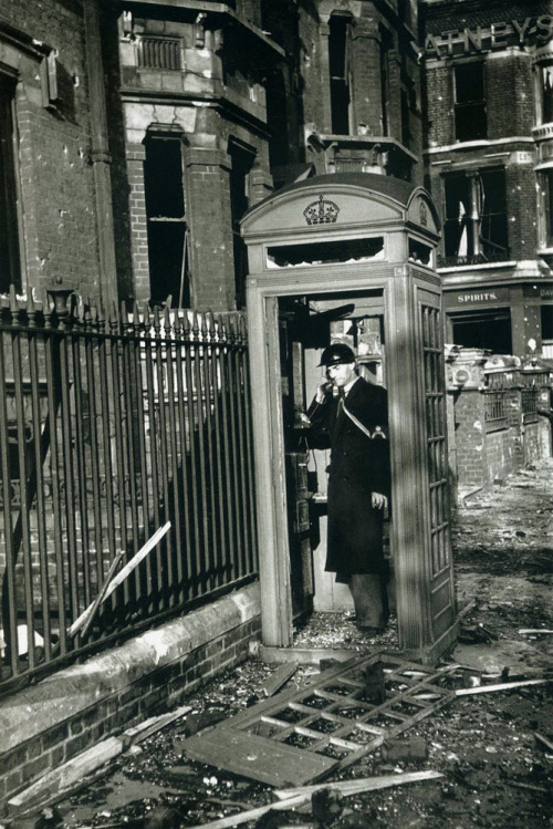 itsjohnsen:  An air-raid warden phones from a shattered booth after a bombing raid. London, 1940. George Rodger