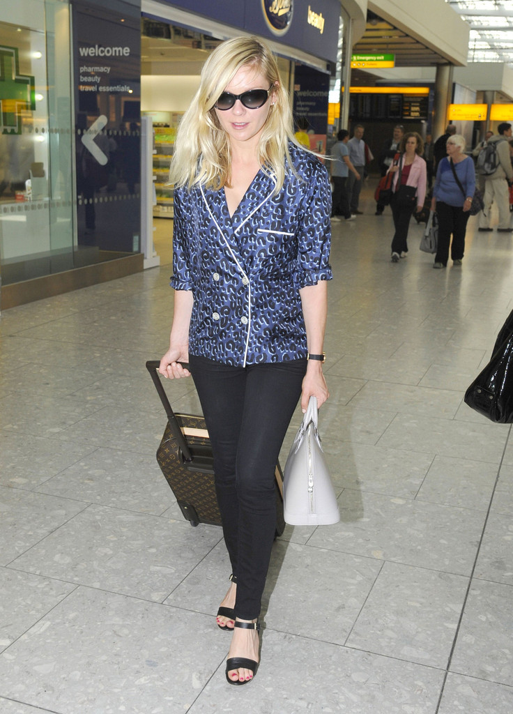 Kirsten Dunst at Heathrow Airport catching a flight to Cannes, May 22nd Louis Vuitton top, purse and luggage, very nice.