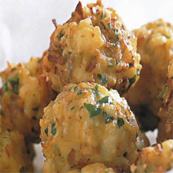 Prawn Bhajis  Prawn bhajis are delicious little snacks that you will probably have to make a double batch of. The prawn and fresh fresh herbs compliment each other so perfectly that you will need every ounce of willpower not to hide them from everybody you made them for. Prawn bhajis or sometimes known as pakoras can also be made using fish or vegetables but whatever type you make, you must have a good chutney to dip them in or a sweet chili sauce. This makes about 2 dozen bite size bhajis. What you need 600g peeled and deveined prawns chopped 1/2 cup flour 1 medium onion finely chopped 3 or 4 green chilis finely sliced Palm of finely chopped fresh coriander (2 to 3 tablespoons) Pinch of bicarb of soda water Salt and pepper Oil for frying The process In a bowl add the flour and then about 2 tablespoons of water. Mix it to a thick batter. If you need slightly more water add another 1 tablespoon. It must be thick and mixed smooth. Use a fork to work out any lumps. Add all the rest of the ingredients and season with a grind of salt and pepper and mix to distribute everything evenly. Heat about 5cm of oil in a pot or frying pan to medium hot, not smoking. To test, drop a cube of bread in the oil and give it 15 seconds and if it is browned and not burned it is the correct heat. Now take tablespoons of the mixture and drop them into the oil. Fry until golden and irresistable. Serve with Chutney as an anytime snack. Try the Kerala country chicken recipe for a perfectly rounded off Indian food meal.