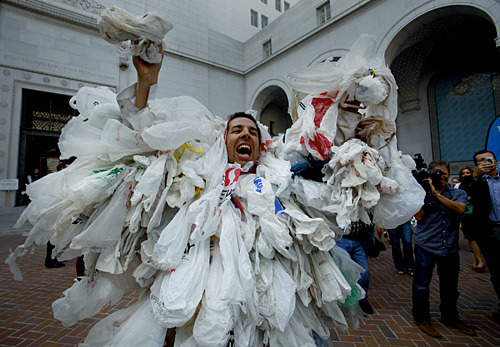 "latimes:  L.A. City Council approves ban on supermarket plastic bags: Los Angeles today became the largest city in the nation to adopt a ban on plastic bags at supermarket checkout lines, handing a major victory to clean-water advocates who sought to reduce the amount of trash clogging landfills, the region's waterways and the ocean. Photo: James Alamillo, playing the ""Bag Monster"" for Heal the Bay, gets into his role while he tries to work up the crowd before the city council voted to ban plastic bags Wednesday. Credit: Mark Boster / Los Angeles Times  What!?"