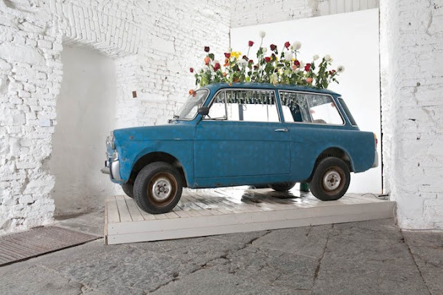 "For his installation titled ""Giardinetta"", artist Manuel Felisi transformed an old Bianchina automobile into a germinator of blossoming new life. The rooftop of the abandoned car functions as a hanging plant rack complete with glass test tubes, while inside the car, and underneath the flowers, rain falls within the compartment and creates a damp, moist world for bacteria and organisms to grow.  (via Junkculture)"