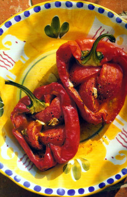 Piedmont Roasted Peppers (Delia Smith's Recipe) Note: I have made these on numerous occasions and they really are simple and very tasty!  Ingredients 4 large red peppers 6 medium tomatoes 8 anchovy fillets drained from a tin 2 cloves garlic 8 dessert spoons Italian extra virgin olive oil Freshly milled black pepper Preheat oven to gas mark 4 (350f /180c) Method Begin by cutting the peppers in half and removing the seeds but leaving the stalks intact (they're not edible but they do look attractive and they help the pepper halves to keep their shape). Lay the pepper halves in the lightly oiled roasting tray. Now put the tomatoes in a bowl and pour boiling water over them. Leave them for 1 minute, then drain them and slip the skins off, using a cloth to protect your hands. Then cut the tomatoes into quarters and place three quarters in each pepper half. After that, snip one anchovy fillet per pepper half into rough pieces and add to the tomatoes. Peel the garlic cloves, slice them thinly and divide the slices equally among the tomatoes and anchovies. Now spoon 1 dessertspoon of olive oil into each pepper, season with freshly milled pepper (but no salt because of the anchovies) and place the tray on a high shelf in the oven for the peppers to roast for 50 minutes to 1 hour. Then transfer the cooked peppers to a serving dish, with all the precious juices poured over, and garnish with a sprig of basil leaves. These do need good bread to go with them as the juices are sublime – focaccia would be perfect.