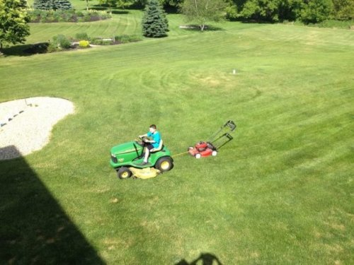 Kid Ties Mower Behind Riding Mower Probably not the most efficient mowing system.