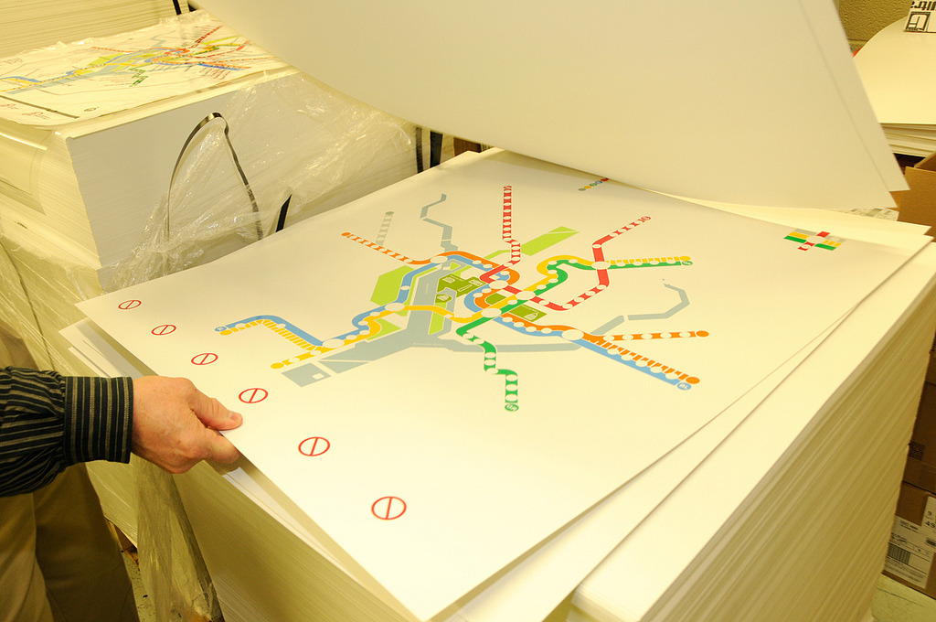How the WMATA Rush+ Maps Are Printed Many thanks to Matt Johnson for telling me about this amazing photoset on Flickr that details the process involved in printing the new Rush+ station maps for Washington, DC's Metro system. Click through to see the whole set! Even as an experienced graphic designer, I was amazed to see that the maps are screen printed - each colour on the map is printed one after the other, each using a separate screen with its own spot colour ink. With a map as complex as this, that means that there are a whopping twelve different colours to print! These being: river blue, park green, National Mall green, Blue Line, Orange Line, Yellow Line, Green Line, Red Line, Silver Line, District/County border grey, Beltway grey, and finally, black. I would have thought with the advances in digital printing and stochastic (micro) screening, that these could be produced digitally in one step instead of twelve, but maybe these are special long-lasting UV inks that will withstand many years of use without fading - an important consideration for station maps! In any case, these photos are a fascinating behind-the-scenes look at a process that many people may not even think about. EDIT: A tweet from a Metro representative confirms that there are THIRTEEN colours used in the printing: 4 greys (Silver Line, Beltway grey, county border grey, and icon grey), 3 greens (parks, Mall, Green Line), 2 Blues (river, Blue Line), Black, Red, Yellow and Orange.