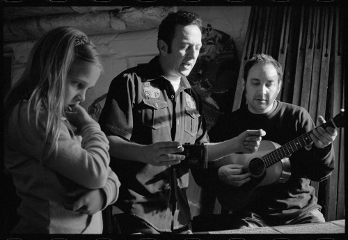 "jimherrington:  Joe Strummer, Smokey Hormel and Joe's daughter - Rick Rubin's garage - West Hollywood, CA © Jim Herrington Beware, this story drops more names than a drunk mailman. I was in Los Angeles shooting an album cover for a Russian bluegrass band… really… and after the photo shoot I was invited to their gig at the Roxy on Sunset Blvd.  I went, and afterwards there was a big party for them next door at the infamous Rainbow Bar & Grill.  There were people I knew from Nashville there, Tony Brown from MCA Records, he'd played piano with Elvis Presley in the '70s, and some others.  At one point Tony spun me around and said, ""Jim, have you met Joe Strummer?""  Well, no I hadn't, and hello Joe.  The night wears on and by the end of the evening it was just Joe and I left sitting at the bar drinking.  I was living in Nashville at the time and Joe was digging whatever country music stories I was spewing out, he really liked old country music.  I finally asked him, ""So Joe, why are you in town?""  He responded with, ""Oh man, you won't believe it… I'm in town to do sing a duet with Johnny Fucking Cash!  In fact I did it earlier today already, up at Rick Rubin's house."" Joe was beside himself, couldn't believe his good fortune, thought he'd died and gone to heaven, as anyone would.  We kept talking and drinking and finally Joe said, ""I'm going back up there tomorrow, you want to come?""  I said well sure and Joe proceeded to draw a ""map"" on the tiny corner of a napkin.  I still have it, by the way… it looks like a chimpanzee tried to write the letter ""Y"" on the back of a postage stamp. Useless, as maps go, but I feel now that it's a cartographic oddity worth saving.   The next morning I arrived at the front gate of Rubin's house a bit hungover, rang the intercom, ""Jim Herrington for Joe Strummer"", and the giant iron gate slowly swung open and I drove in.  The driveway circled around your typical Hollywood Hills 1920's Mediterranean-style mansion, owned at some point by this or that silent film star, I forget which one, and I arrived at the back of the house where Joe comes strolling out of the garage with a big grin saying, ""Hello mate, you made it!""  Maybe he remembered the map and was surprised as well… I went into the garage with Joe and every horizontal surface was covered with large sheets of 13 x 19 sketching paper filled with song lyrics written in black Sharpie.  On tables, on the floor, all across Rubin's yellow Corvette, lyrics everywhere.  I asked what he was up to and Joe said, ""Well, I've really already done my bit with Johnny yesterday, I'm not even supposed to be here… now I'm just trying to write a song to pitch to him."" He rolled a joint, we smoked it and he started telling me about the song… that maybe it could be about Johnny Cash, or a guy like him… but Johnny could sing it. Kind of autobiographical. Lots of Southern imagery. Then he says, ""You're from the South, help me out."" So I threw out some lines and he liked one, ""King Cotton's down the road"" and he wrote it down. At that point, Cash, who'd been inside recording with Rubin, was leaving and he came out through the garage, looking a bit more frail than when I'd last seen him. We said hello, I'd met him a couple of times before. After Cash was gone Joe and I took some photos then went to Rubin's kitchen to make some tea - Joe: ""Fuck, does he ONLY drink green tea?"" and then went down to the studio and I met Rubin and Smokey Hormel, who was playing guitar on some of the tracks. The day goes on, we do some more photos, Joe records a demo of the song, finally it's late afternoon and I have to leave.  I stayed in touch via email with Joe until his sad and untimely death less than a year later. I sent his wife a print of one of the photos I took of Joe, Smokey and Joe's daughter, which she apparently displayed somewhere in their house because later on I got a call from Damien, a family friend who had seen the photo there and was touched by the picture of his friend and inquired if he might be able to buy a print for himself.  Seeing as it was a family friend, and due to the circumstances involved, I charged a very nominal fee, basically the price of printing and shipping it over to England.  A few weeks later he gave me another call to say he'd received it and thanks.  He was calling from his house in Jamaica this time and I learned that ""Damien"" was, in fact, Damien Hirst, who with a net worth of around $300 million dollars is the richest artist in the history of art. And to think that I rounded off the FedEx charges in his favor… More time goes by and I'm tucked into a booth in a crowded coffee shop one day, having lunch.  A guy I vaguely know walks in and as he's walking past my table looks at me and mumbles, ""Your song's on that album…""   ""My song…? What song, what album?""  ""The one you wrote with Joe Strummer.""   I'd apparently told him the story at a party one night and he'd remembered it.  And sure enough, the song in question, Long Shadow, had shown up on a posthumous release of Joe's last album with his band The Mescaleros. Now, I never claim I ""co-wrote"" a song with Joe, but I did get the record… and sure enough, there's that line…   But years later I still can't help wondering, did Johnny Cash ever record it, as Joe had intended, and did he sing my line?  This tale is all kinds of awesome. Jim Herrington's one cool dude, folks."